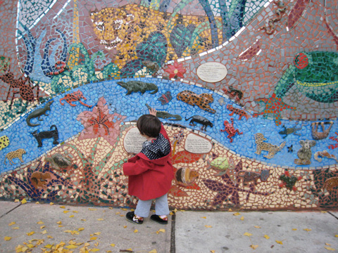 Blackbird, wearing a red coat, walks along a mosaic wall of animals in the jungle, and touches it with her right hand.
