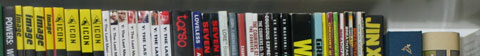 A row of graphic novels' spines, cropped to show only the top.