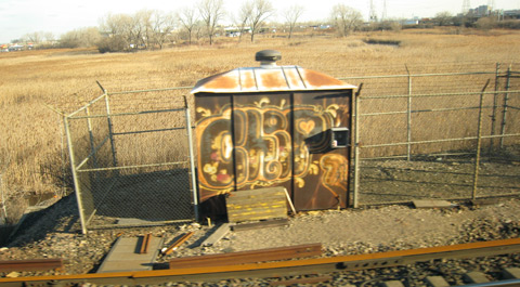 A small, rusted metal shed surrounded on three sides by fencing, that has old graffiti on it reading 'Chip' in embellished bubble letters.