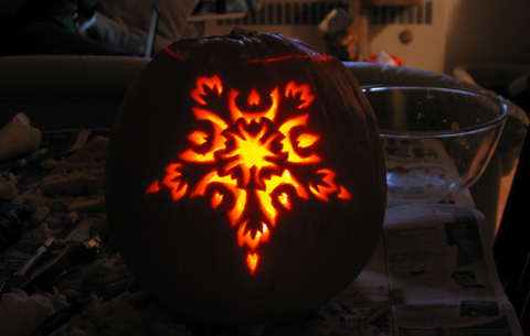 My pumpkin, lit up, with an ornate pentragram-eqsue design.