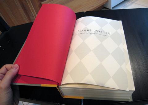 The title page of the book, which has faint grey a diamond pattern covering the page, sits in a spread with a vibrant red sheet that also serves as the inside covers.