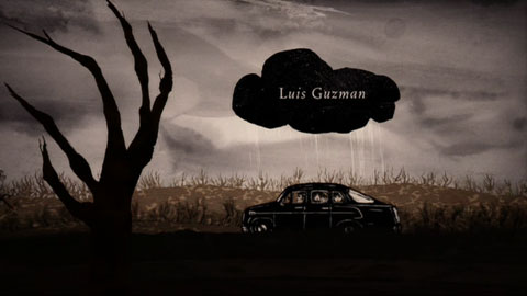 The car, seen from the side, drives down a spooky, overcast country road, underneath a small black rain cloud that hovers over them persistently. Inside the cloud are the credits.