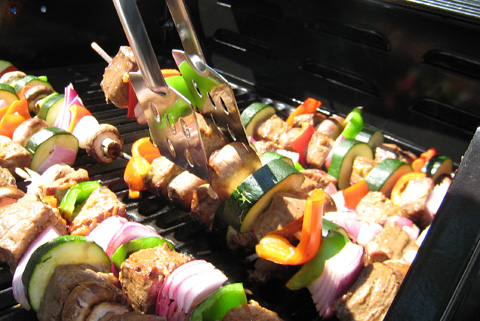 Skewers of steak, peppers, mushrooms, red onions, and zucchini on the barbecue, being turned with metal tongs.
