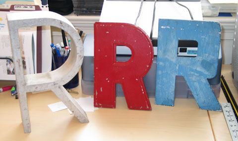 Three metal sign capital Rs. One brushed aluminum, one blue and blocky, one red and geometric grotesque, I think.