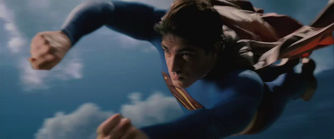 A closeup of Superman flying fast through a cloudy sky.