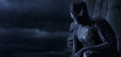 Spider-Man, in his black suit, looks a the viewer through the rain.