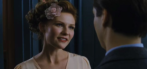 Mary Jane Watson, wearing a dress and flower-shaped ornament in her hair, talks to Peter.
