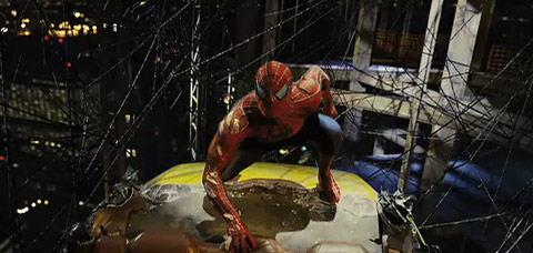 Spider-Man, in his regular blue and red suit, crouches on a yellow cab, caught in a black web above the city.