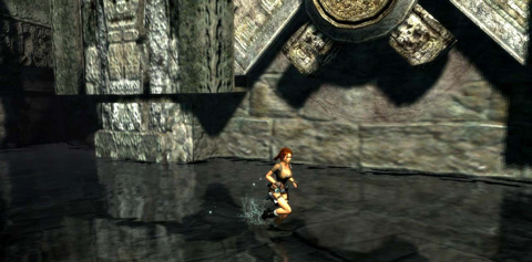 Lara runs in shallow water past a large stone device that looks like a cog.