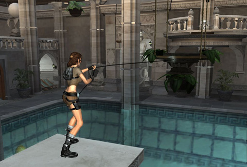 Lara stands on a pillar in her pool, pulling a hanging platform with her grappling hook. The pool room has an old English mansion feel, with plenty of gray carved stone features.